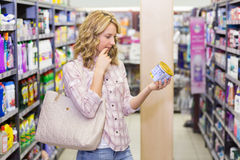 Vue de côté d'une femme assez blonde regardant un produit Photo libre de droits