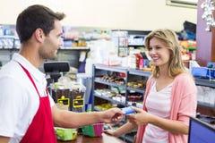 Vue de côté d'une femme de sourire à la caisse enregistreuse payant avec la carte de crédit photo libre de droits
