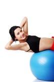 Vue de côté d'une femme s'exerçant sur la boule de forme physique Photo stock