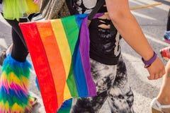 Vue de côté d'une fille de marche hodling un homosexuel gai d'arc-en-ciel Image libre de droits