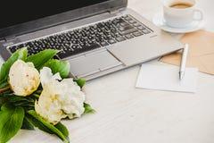 Vue de côté d'une plate-forme avec l'ordinateur, du bouquet des fleurs de pivoines, de la tasse de café, de la carte vide et de l Images stock