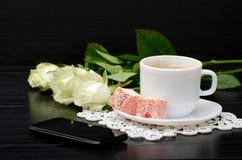 Vue de côté d'une tasse de café avec du lait, bonbons orientaux smartphone, roses blanches Images stock