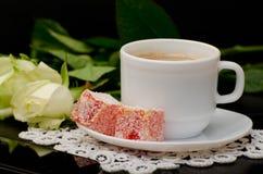 Vue de côté d'une tasse de café avec le plan rapproché de lait, bonbons orientaux smartphone, roses blanches sur un fond noir Images libres de droits