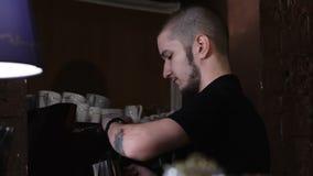 Vue de côté de barman poussant le bouton sur la machine de café banque de vidéos