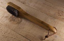 Vue de côté de brosse de nettoyage pour le barbecue sur le bois rustique Photos libres de droits