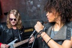 Vue de côté de femme chantant dans le microphone avec l'homme jouant la guitare Image libre de droits