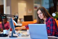 Vue de côté de femme d'affaires heureuse travaillant sur son ordinateur portable dans le bureau Photo stock
