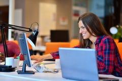 Vue de côté de femme d'affaires heureuse travaillant sur son ordinateur portable dans le bureau photos libres de droits