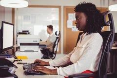 Vue de côté de femme d'affaires travaillant sur l'ordinateur au bureau Image stock