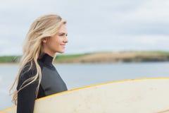 Vue de côté de femme dans le vêtement isothermique tenant la planche de surf à la plage Images libres de droits