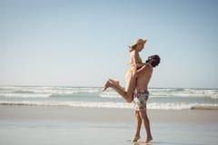 Vue de côté de femme de levage de l'homme à la plage Images libres de droits