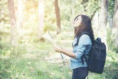 Vue de côté de femme de voyageur recherchant la bonne direction sur la carte Images libres de droits