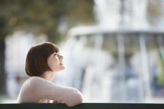 Vue de côté de femme en Front Of Blurred Fountain Photo stock