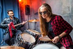 Vue de côté de femme jouant les tambours et l'homme chantant dans le microphone Image libre de droits
