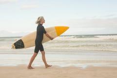 Vue de côté de femme marchant avec la planche de surf sur le rivage photo stock