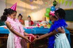Vue de côté de fille donnant le cadeau à l'ami Photos libres de droits