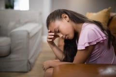 Vue de côté de fille fatiguée se reposant sur le sofa photographie stock