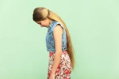 Vue de côté de fille triste d'adolescent, seul punie au mur vert photographie stock