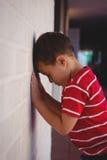 Vue de côté de garçon triste se penchant sur le mur Image libre de droits