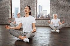 Vue de côté de groupe tandis que formation de yoga Photographie stock