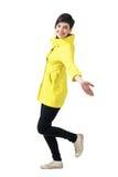 Vue de côté de jeune femme gaie dans l'imperméable jaune fonctionnant avec les bras répandus regardant l'appareil-photo Photographie stock libre de droits