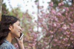 Vue de côté de jeune femme parlant au téléphone dehors en parc dans le printemps Images libres de droits