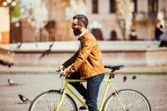 Vue de côté de jeune homme barbu beau dans des lunettes de soleil semblant parties tout en montant sur sa bicyclette dehors Image stock