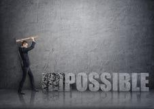 Vue de côté de jeune homme d'affaires se brisant le béton 3D et le x27 ; impossible& x27 ; mots avec un marteau Image libre de droits