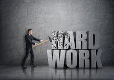 Vue de côté de jeune homme d'affaires se brisant le béton 3D et le x27 ; work& dur x27 ; mots avec un marteau Images libres de droits