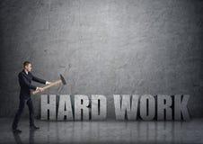 Vue de côté de jeune homme d'affaires se brisant le béton 3D et le x27 ; work& dur x27 ; mots avec un marteau Image libre de droits