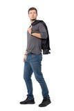 Vue de côté de jeune homme occasionnel marchant avec la veste au-dessus de l'épaule regardant derrière Photographie stock libre de droits
