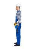 Vue de côté de jeune travailleur de la construction dans la ceinture d'uniforme et d'outil Images libres de droits