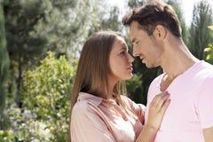 Vue de côté de jeunes couples affectueux regardant l'un l'autre en parc Images libres de droits
