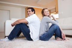 Vue de côté de jeunes couples se reposant sur l'étage dos à dos Photos stock