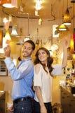 Vue de côté de jeunes couples se tenant de nouveau au dos dans le magasin de lumières Photo stock