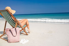 Vue de côté de jolie brune détendant sur la chaise de plate-forme à la plage Photographie stock libre de droits