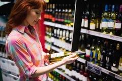 Vue de côté de jolie femme choisissant soigneusement une bouteille de vin Image stock