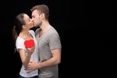 Vue de côté de l'homme embrassant la femme avec le coeur à disposition sur le noir Photo libre de droits
