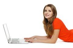 Femme se trouvant sur le plancher avec son ordinateur portable Photos stock