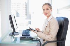 Vue de côté de la femme d'affaires blonde à l'aide de la calculatrice Images stock
