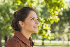 Vue de côté de la femme mignonne de brune portant un manteau brun Image libre de droits