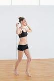 Vue de côté de la femme sportive satisfaite tenant une corde à sauter images libres de droits