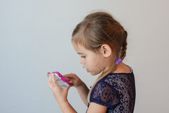 Vue de côté de la fille sérieuse de quatre ans tapant le téléphone intelligent Image stock