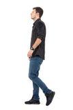 Vue de côté de la marche de port de jeans et de chemise de jeune homme Image libre de droits