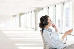 Vue de côté de la musique de écoute de mi femme d'affaires adulte par des écouteurs dans le bureau vide Images libres de droits