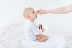 Vue de côté de parent jouant avec le bébé garçon adorable s'asseyant sur le lit Image libre de droits