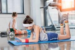 Vue de côté de petite fille dans des écouteurs se trouvant sur le tapis de yoga et à l'aide du smartphone dans le gymnase Images stock