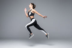 Vue de côté de sauter sportif de jeune femme d'isolement sur le fond gris photo stock
