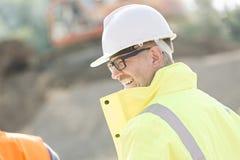 Vue de côté de surveillant masculin heureux au chantier de construction Images libres de droits