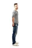 Vue de côté de type convenable de jeunes dans les jeans et des espadrilles Photographie stock